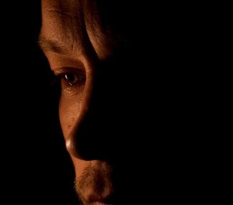 un rostro iluminaod por una vela sobre un fondo negroy del que solo se aprecia medio rostro