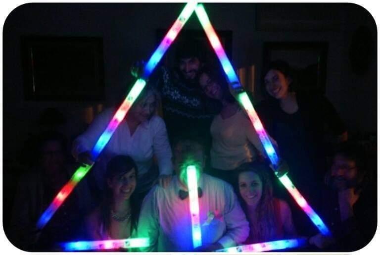 Foto de una celebración navideña con un pino de navidad hecho de luces