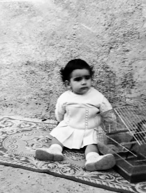 niña morena sentada en una alfombra en mitad de un solar (fotografía familiar de Henar Tejero)