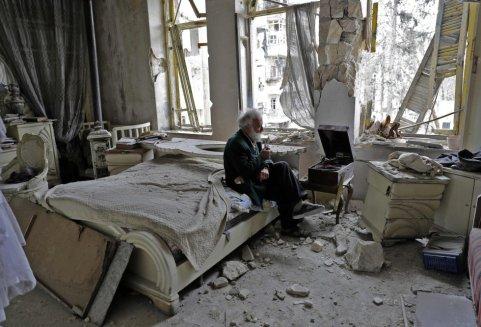 Un anciano de barba y pelo canos escucha un disco en un tocadiscos sentado en una cama de matrimonio en medio de una habitación destrozada por una explosión. En la ciudad de Alepo (Siria) durante la guerra.