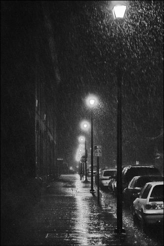 Imagen nocturna de una calle lluviosa con una acera llena de charcos y varias farolas encendidas.