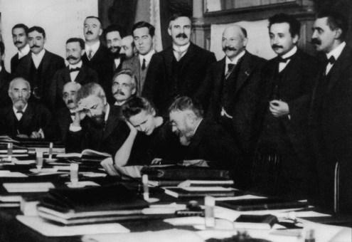 Fotografía del congreso Solvay de 1911 con una serie de científicos de pie y otros entre los que se encuentra Marie Curie sentados en una mesa llena de carpetas de documentos y libros.