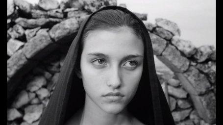 """Fotograma de """"El Evangelio según San Mateo"""" (""""Il vangelo secondo Matteo"""", Pier Paolo Pasolini, 1964), en el que se ve el rostro de una chica con una toca negra delante de los restos de un arco de piedra."""