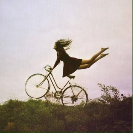 Una joven descalza con un vestido rojo flota sujeta del manillar de una bicicleta de mujer mientras la bicicleta levanta la rueda delantera.