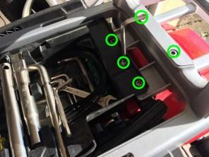 Schrauben vom Werkzeugfach und Gepäckbrücke lösen.