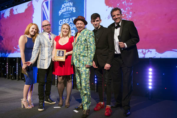 German comedy ambassador Henning Wehn presents the award to the Roebuck Inn team