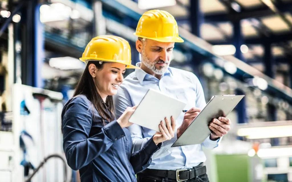 Zwei Mitarbeiter mit gelben Bauhelmen sehen sich etwas auf einem Tablet an