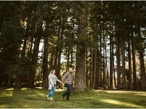 couple walking in the forest during a spring engagement session at lake wilderness in maple valley wa