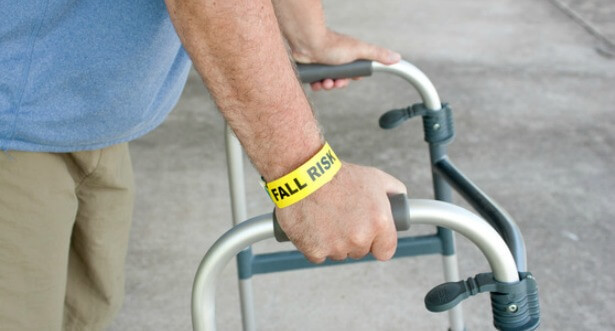 An elderly man wearing a fall risk bracelet around his wrist using a walker