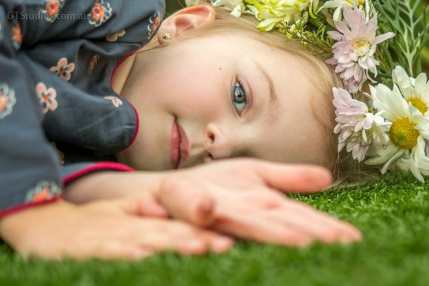 Girl laying on grass, in pretty dress with flower crown, one eye obscured