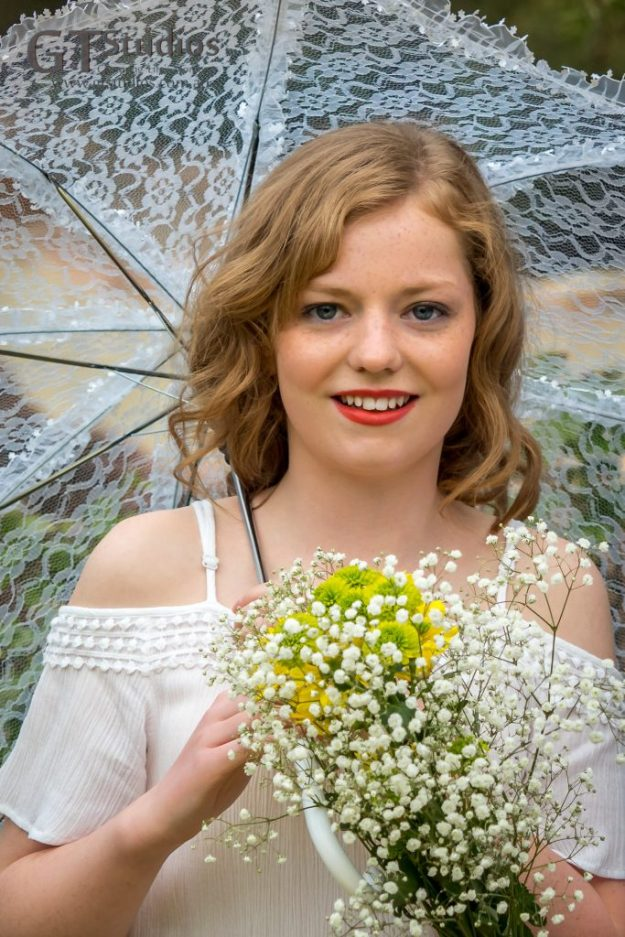 Mikayla with a white lace parasol and a bunch of fresh flowers