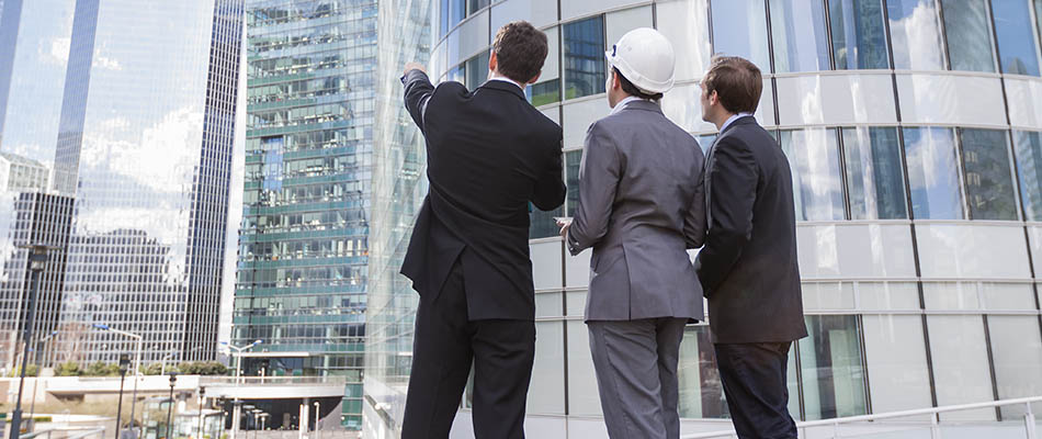 three men in construction hats and suits