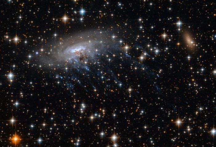 Spiral Galaxy Being Torn Apart Captured by Hubble [Video]