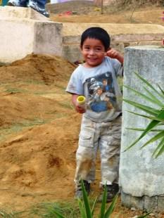 little boy behind grave