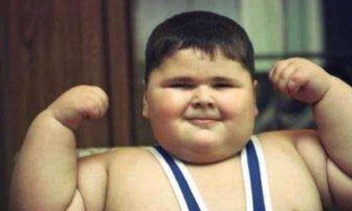 толстый мальчик показывает бицепс и улыбается