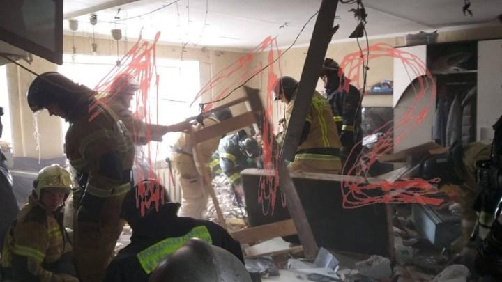 Разрушенная квартира, в которой работают спасатели