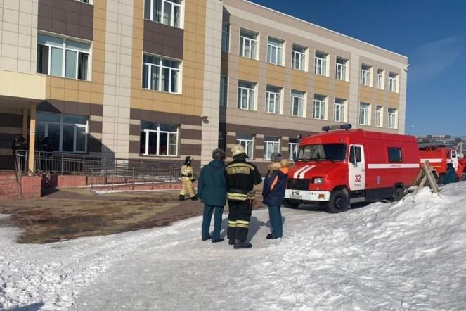 Красная пожарная машина и мужчины в синей форме стоят на улице