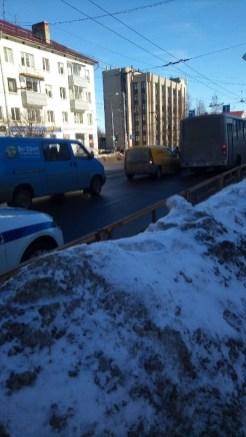 Машина ДПС стоит рядом с автобусом на фоне сугроба