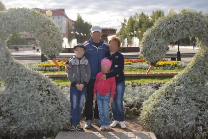 Отец и мать с дочерью и сыном стоят обнявшись на улице около лебедей из растений