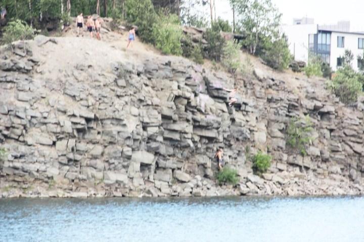 Люди прыгают со скалы