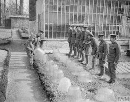 Men under instruction at the Agriculture Directorate farm at Roye attending a demonstration of the use of the 'cloche'. Near Amiens, 18 March 1918.