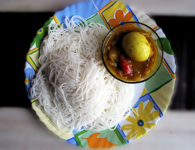 Idiyappam (string hopper) is a really popular dish enjoyed by all the Kerala people. It is made from rice flour. The flour is first made into a dough by mixing with hot water and then it is squeezed using a rice noodle maker. then is is steamed using a pressure cooker.