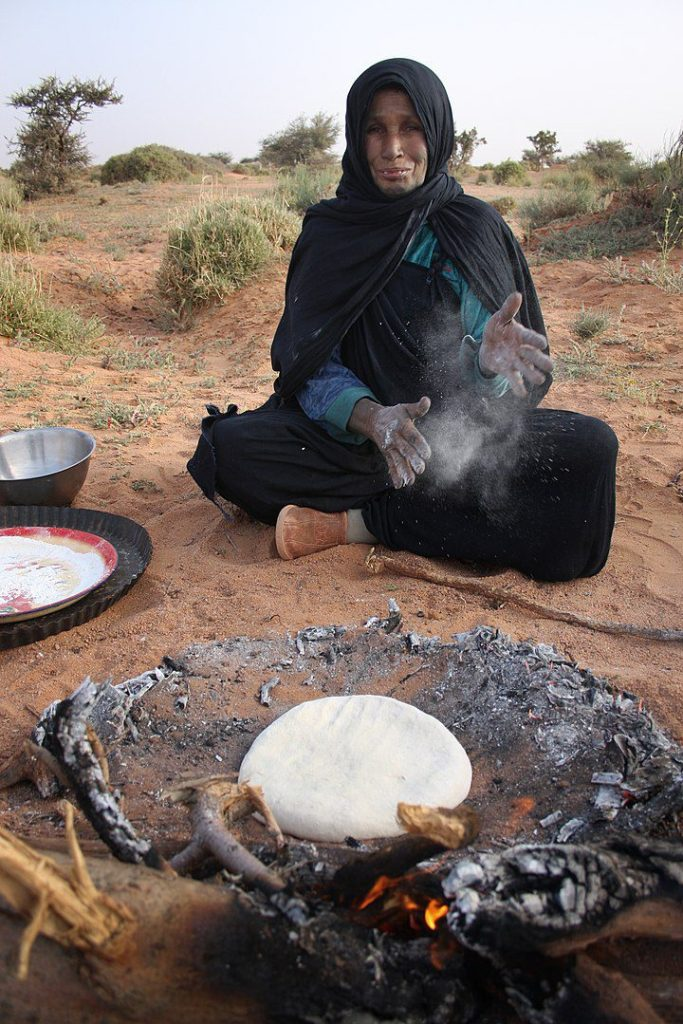 A Sahrawi makes bread in the ashes from a fire.