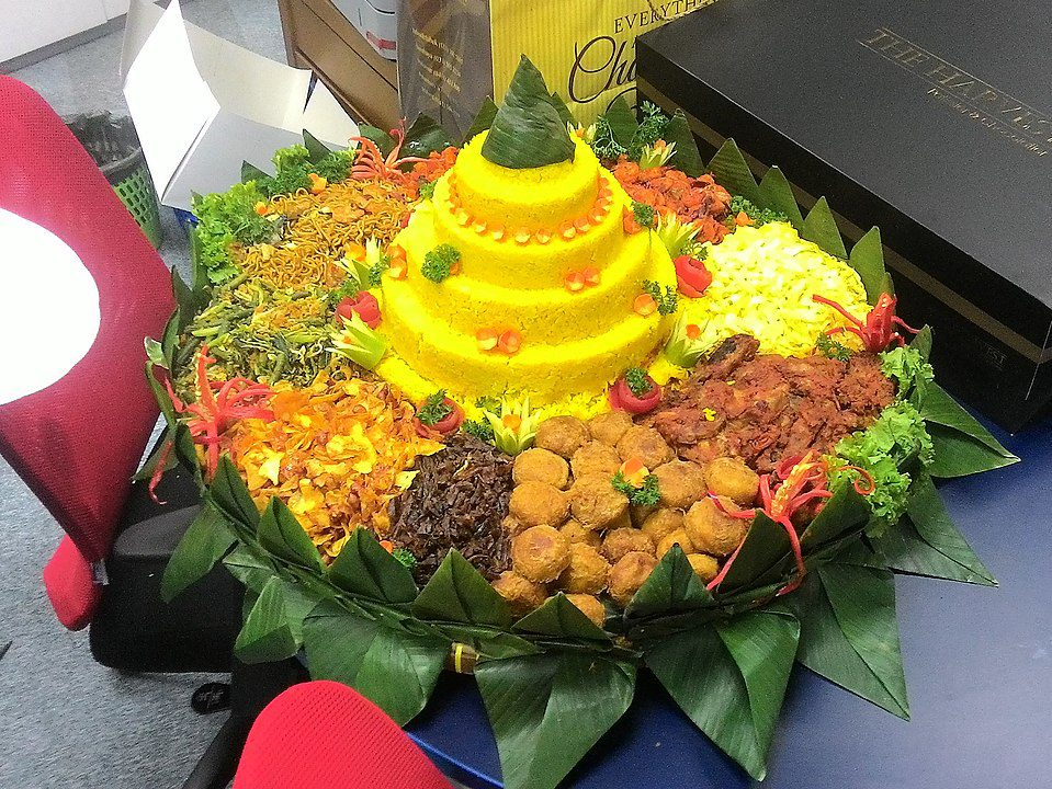 Tumpeng is an Indonesial cone-shaped rice dish with side dishes of meat and vegetables. Tumpeng dates back to ancient Indonesian tradition that revered mountains as the abode of hyangs, the spirit of ancestors and gods. The cone-shaped rice meant to mimics the holy mountain. The feast served as a thanksgiving for the abundance of harvest or any other blessings.