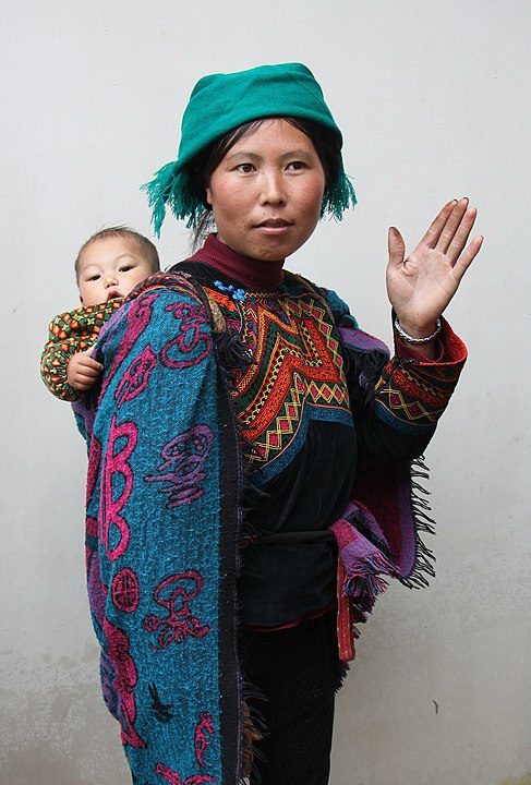 Yi woman in traditional dress with a child