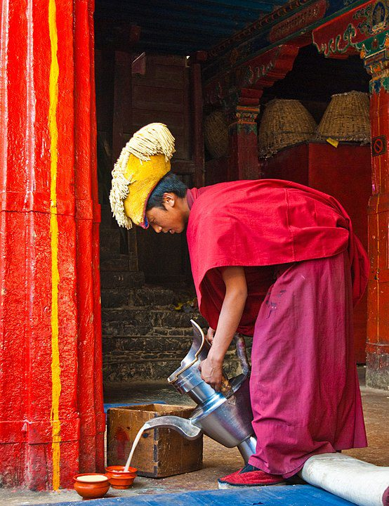 A monk pouring butter tea