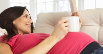 Pregnant Woman Drinking Hot Drink And Reading Book At Home