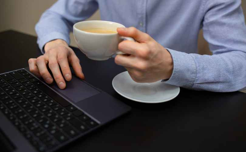 anonymous businessman drinking cappuccino and working on netbook in office