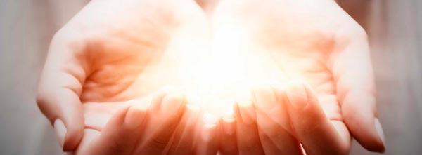 mãos com luz enviando reiki à distância