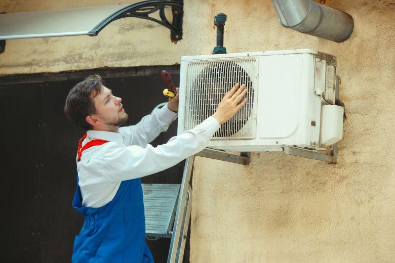 técnico instalando ar-condicionado, atento à escolha do disjuntor para ar-condicionado