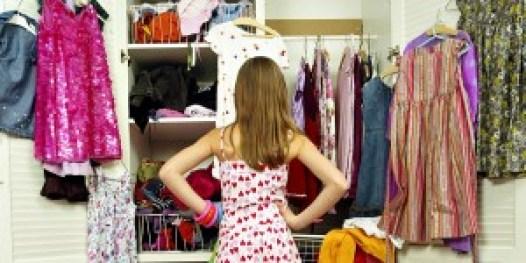 Girl (9-11) looking in wardrobe, hands on hips, rear view --- Image by © Ocean/Corbis