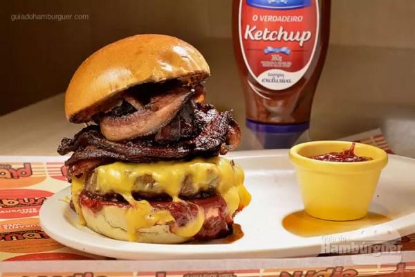 The Bacon Tower: Hambúrguer de Angus Beef ( blend exclusivo da casa) de 180g, grelhado no char broiler e coberto por queijo do reino derretido e camadas de bacon, lombo defumado e pancetta (todos produzidos artesanalmente em Quiririm, interior de SP). Servido no pão brioche com o exclusivo Ketchup de framboesa da Hellmann´s. - R$ 35 - SP Burger Fest