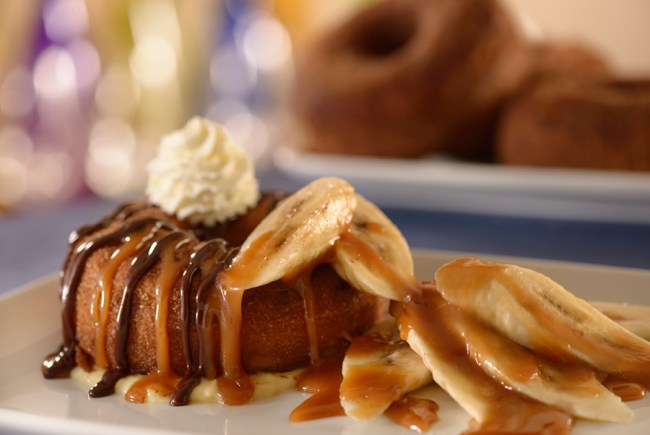 Be Our Guest Breakfast: croissant donut topped with bananas, caramel sauce, chocolate ganache, and whipped cream.