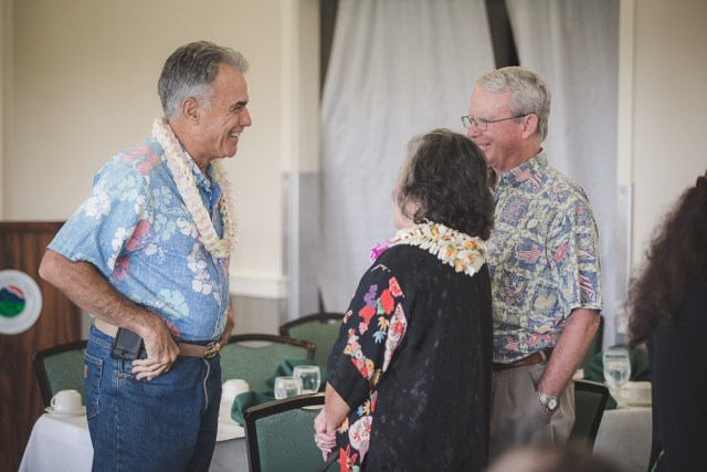 A man wearing a lei, speaking with a senior couple.