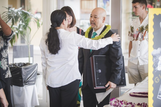 Ernie Martin entering an event wearing a suit and tie and lei.