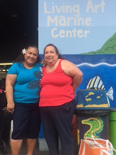 Two women stand in front of the Living Art Marine Center signage.