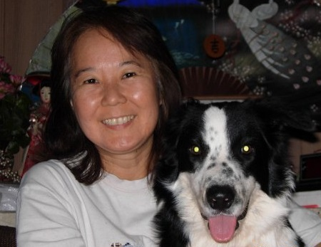 A woman smiling as she holds her border collie dog beside her. The dog appears to be smiling with her.