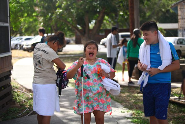 A group of teens are heading to the pool. One girl is adjusting her backpack, turning her back to the camera and showing a Camp Get Ahead t-shirt. The boy on the right wears his towel around his neck and smiles as he looks toward the girl in the middle - who is holding her white cane in one hand and towel in the other. She has an enormous smile as she's in the middle of laughing.