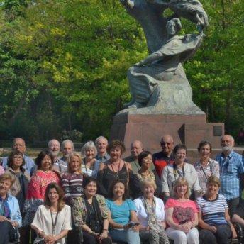 Zdjęcie grupowe w Łazienkach z pomnikiem Chopina podczas półdniowego zwiedzania miasta. Małgorzata w środku.