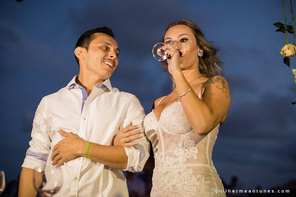 Foto de Casamento na praia de Larissa e Ronaldo noiva bebendo o brinde de tradição