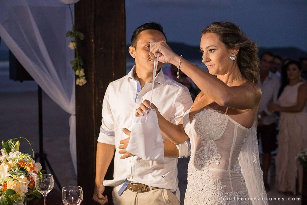 Foto de Casamento na praia de Larissa e Ronaldo abrindo presente de casamento