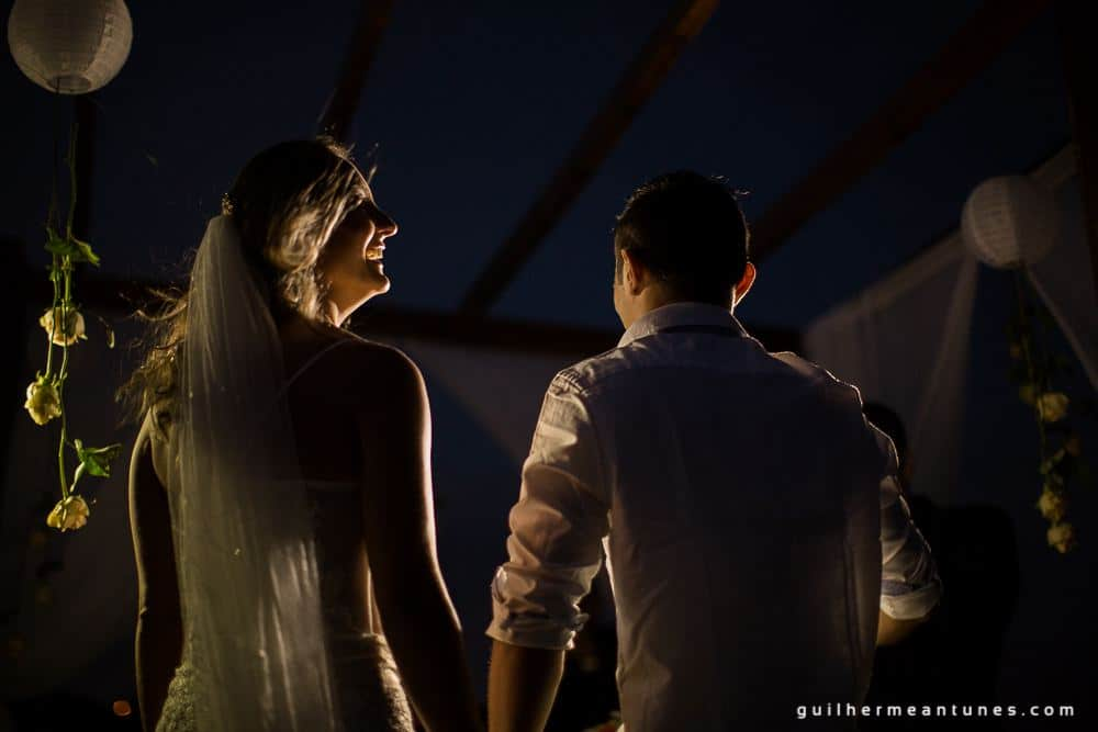 Foto de Casamento na praia de Larissa e Ronaldo de mãos dadas de costas a noite