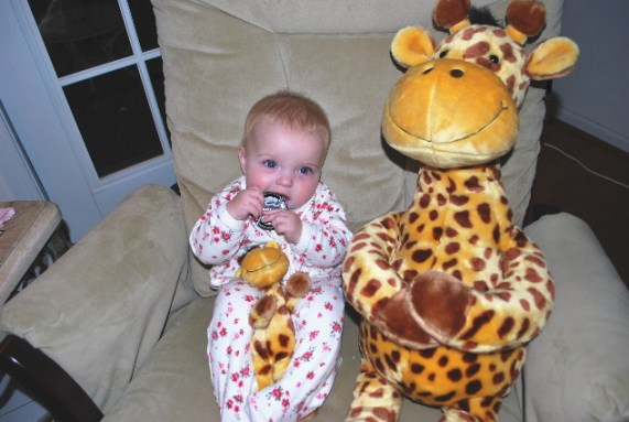 Mama Giraffe, baby giraffe, and little lens cap hangin out with me on Nana's rocker.