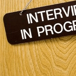 "A screenshot of the corner of a photo of an ""interview in progress"" sign"
