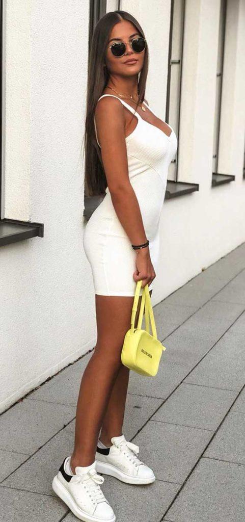 Christina Alexia com vestido branco e bolsa amarel