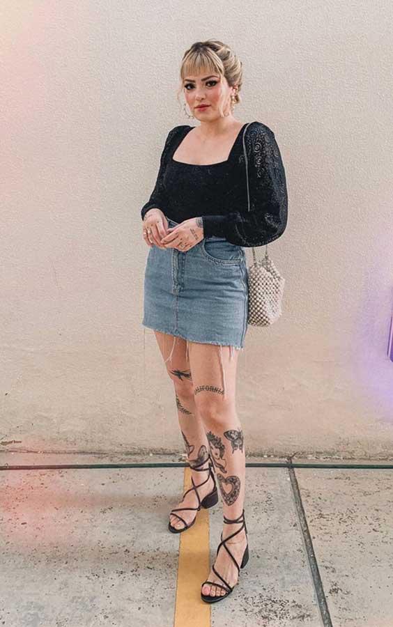 look de churrasco com blusa preta com manga bufante e minissaia jeans